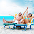 Rear view of a couple on a deck chair relaxing on the beach - Foto Stock