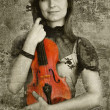 Beautiful female violinist playing violin on the grunge backgrou — Foto Stock
