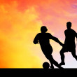 Silhouettes of footballers on the sunset sky - Stockfoto