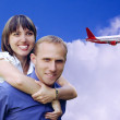 Happy couple  on blue sky with airplane background — Stock Photo