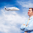 Happy businessman on blue sky with airplane — Stock Photo