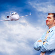 Happy businessman on blue sky with airplane — Stock Photo #6357267