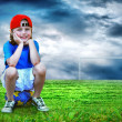 Young boy seating on the ball in green field - Stock Photo