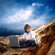 Child with laptop on the mauntain under sky with clouds — Stock Photo