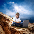 Royalty-Free Stock Photo: Child with laptop on the mauntain under sky with clouds