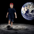 Child football player and Grunge ball on the dark background — Stockfoto