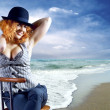 Young woman in black hat seating on the beach — Stock Photo