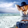 Young woman in black hat seating on the beach — Foto de Stock
