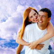 Young love couple smiling under blue sky — Stok Fotoğraf #6357934