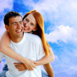 Young love couple smiling under blue sky — Stock Photo #6357935