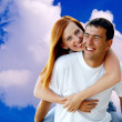 Young love couple smiling under blue sky — Stock Photo #6357939