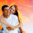 图库照片: Young love couple smiling under blue sky