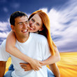 Young love couple smiling under blue sky — Stok Fotoğraf #6357946