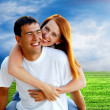 Foto Stock: Young love couple smiling under blue sky