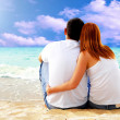 Sea view of a couple sitting on beach. — Stock Photo #6357957