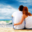 Foto Stock: Seview of couple sitting on beach.