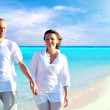 View of happy young couple walking on the beach, holding hands. — Stock Photo #6358016