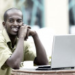 Young happy man or student with laptop sitting at the table — Stock Photo