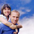Young love couple smiling under blue sky — Stok fotoğraf