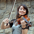 Playing violinist on the grunge background - Stock Photo