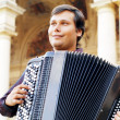 Male playing on the accordion against a grunge background — Stock Photo