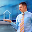 Stock Photo: Happy businessman with house in his hand