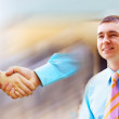 Man on background of Shaking hands of two business — Stockfoto