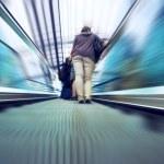 Passangers with bag on railway station escalator — Stock Photo