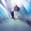 Passangers with bag on railway station escalator - Stock Photo