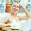 Happy woman in white with cup of coffee or tea at bedroom — Stockfoto