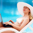 Royalty-Free Stock Photo: Young women relaxing near waterpool with laptop.