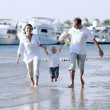 View of happy young family having fun on the beach — Stock Photo #6358898
