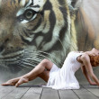 Woman dancer seating posing on wild annimals background — Stockfoto