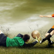Shoot of football player and goalkeeper on the outdoors field - Stock Photo