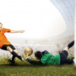 Shoot of football player and jump of goalkeeper on the field of - Stock Photo