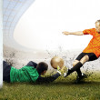 Foto Stock: Shoot of football player and jump of goalkeeper on field of