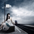 Girl waiting train on the platform of railway station — Stockfoto