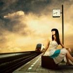 Girl waiting train on the platform of railway station — Stock Photo