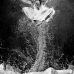 Jump of ballerina on the ice dancepool around splashes of water — Stock Photo #6359536