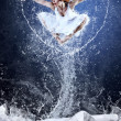 Jump of ballerina on the ice dancepool around splashes of water — Stock Photo
