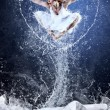 Foto Stock: Jump of ballerinon ice dancepool around splashes of water