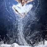 Jump of ballerina on the ice dancepool around splashes of water — Stock Photo #6359541