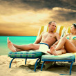 Rear view of a couple on a deck chair relaxing on the beach — Stock Photo