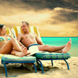 Rear view of a couple on a deck chair relaxing on the beach — Stock Photo #6359574