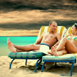 Rear view of a couple on a deck chair relaxing on the beach — Stock Photo #6359575
