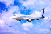 Airplane at fly on the sky with clouds — Stock Photo