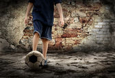 Football player and Grunge ball on the retro grunge background — Stock Photo