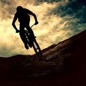 Silhouet van een man op muontain-bike, zonsondergang — Stockfoto
