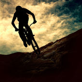Silhouette of a man on muontain-bike, sunset — Stok fotoğraf