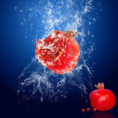 Water drops around red fruit on blue background — Stock Photo